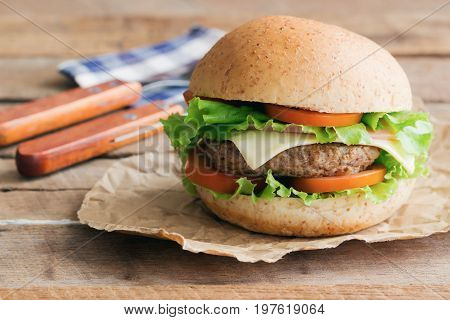 Homemade hamburger or sandwich on brown paper. Delicious sandwich hamburger with meat or pork ham cheese and fresh vegetable. Hamburger or sandwich is the popular fast food for brunch or lunch. Cheese burger ready to served on table.