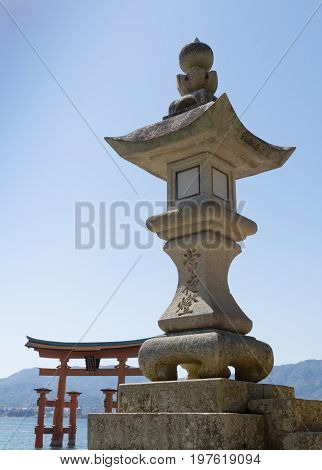 Close up of an engraved concrete shrine with the Torii Gate of Miyajima in the background.