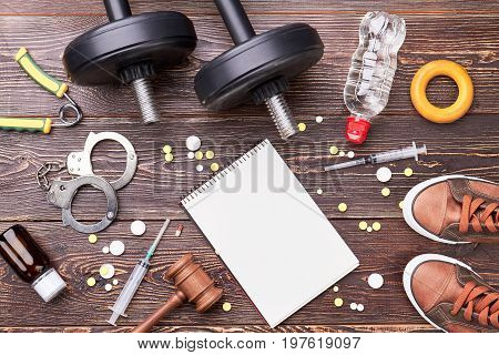 Dumbbells, handcuffs, syringe, pills, gavel. Background of sport equipment and pharmaceutical steroids for sportsmans.