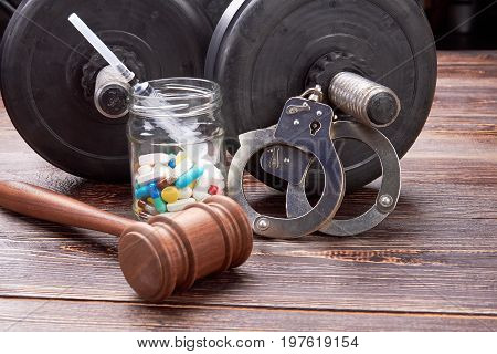 Gavel, jar with pills, handcuffs, dumbbells. Dumbbells, pills, syringe, handcuffs, gavel. Sports with drugs and law.