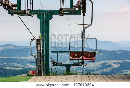 Empty Ski Elevator With Red Chairs On Top Of A Hill