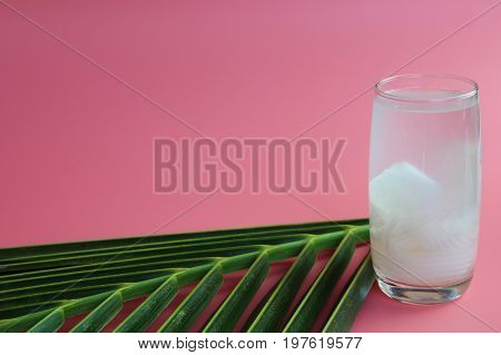 Fresh  coconut water in glass Ready to drink with leaf on  pink background, summer and healthy concept.