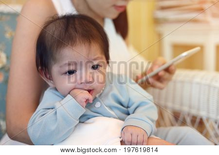 Cute Baby Boy Sucking Finger Hand With Mother Playing Mobile Phone