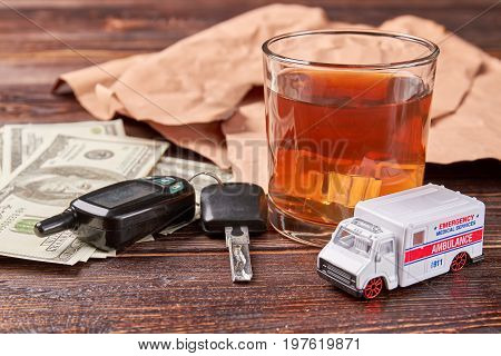 Alcohol drink and keys. Money, car keys, glass of whiskey, ambulance on wooden background. Drunk driving concept.
