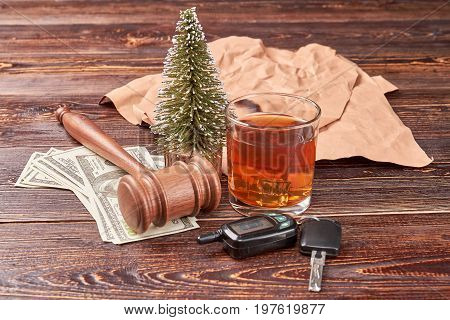 Gavel on dollars, key, alcohol. Glass of whiskey beside car keys and gavel with money on wooden background.