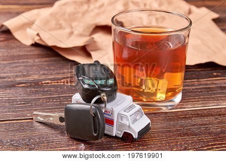 Car key on toy ambulance. Ambulance, car key, whiskey, paper on wooden background. The concept of drink driving.