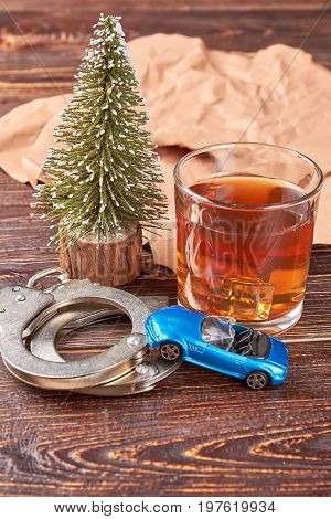 Car, handcuffs, glass of whiskey. Tumbler glass with alcohol, handcuffs, toy car on brown wooden background.