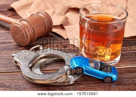 Gavel, handcuffs, car, whiskey, paper. Booze driving concept.