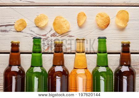 Still life from beer and chips. Bottles with beer and unhealthy fried crispy potato.