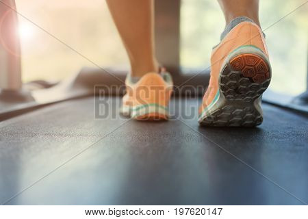 close-up footwear image human jogging exercise on run treadmill machine cardio equipment at sport healthy club center