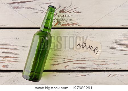 Alcohol, paper message, vintage background. Single bottle isolated on wooden background.