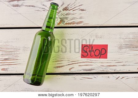 Lying bottle, red paper message. Stop drink and make your life better.