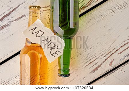 Alcohol abuse, how to stop. Full bottles of alcohol beverages, torn papers sheet with text, old floor. Ways to beat booze.