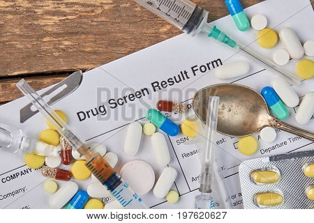 Drug screen result form, syringes, pills. Different pills, spoon, syringes close up. Drugs dependence and injections.