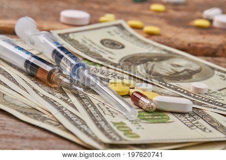 Dose of narcotics for cash. Injections for junkie, money, wooden table.