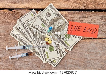 Narcotics abuse leads to death. Money, syringes, pills, text the end.