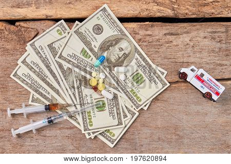 Narcotics not save from pain. Syringes, pills, money, emergency ambulance, wooden background.
