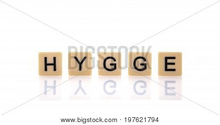 HYGGE spelt on word tiles on a white background Hygge is a Danish and Norwegian word which can be described as a quality of cosiness and comfortable conviviality that engenders a feeling of contentment or well-being.