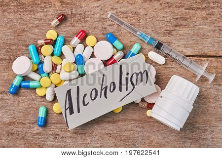 Heap of pills, syringe, container, message. Treatment of alcohol addiction.