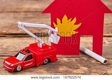 Toy fire engine extinguishes flaming house. Careless handling of fire dangerous for life