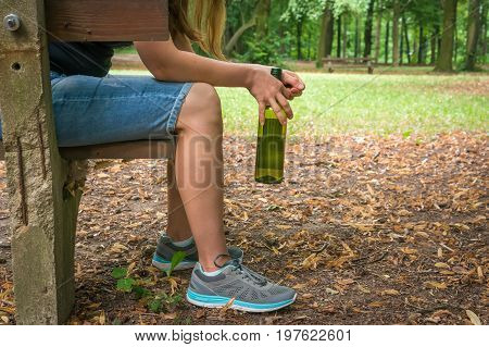Unhappy woman drinking wine in the park and sitting on a bench - alcoholism concept