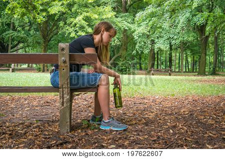 Woman Drinking Wine In The Park And Sitting On A Bench