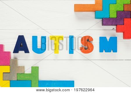 Word Autism built of colorful wooden blocks on a white wooden background with copy space top view. Concept of autism word flat lay. Autism Spectrum Disorder (ASD).