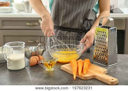 Young woman whisking eggs for carrot cake in kitchen