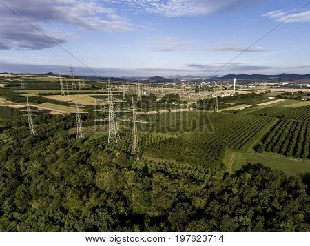 Aerial view High voltage metal post. High-voltage tower. Top view green landscape tree plaantage fruit produce