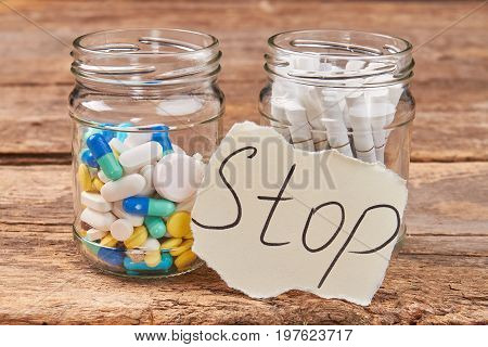 Cigarettes and pills, wooden background. Jars with pills and cigarettes. Stop nicotine addiction concept.