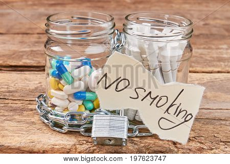 Pills and cigarettes, paper message. Pills, cigarettes, chain, padlock, message, wooden background. No smoking tobacco concept.
