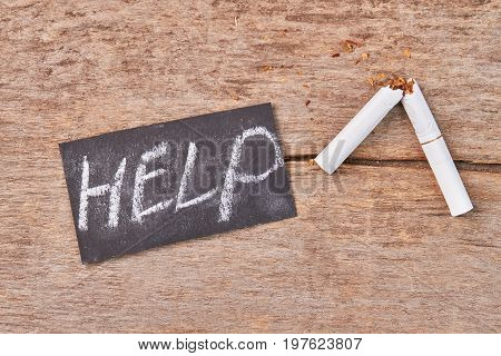 Broken cigarette on wooden background. Message help, broken tobacco cigarette, old wooden table.