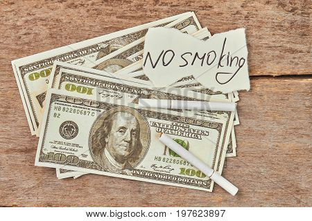 No smoking concept. American money, cigarettes, paper message.