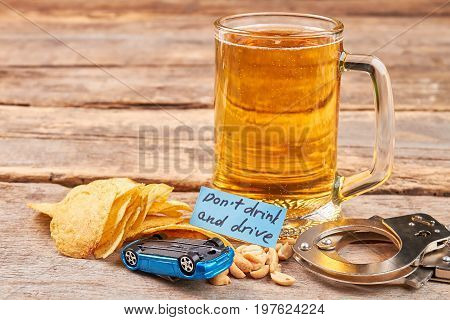 Do not drink and drive concept. Beer, handcuffs, chips, turned over car, wooden background.