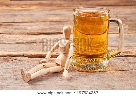 Human wooden dummy and beer. Beer addiction concept.