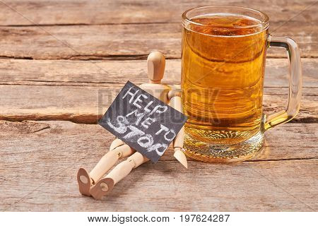 Help to stop alcohol addiction. Human wooden dummy, message, rustic glass of beer, old wooden background.