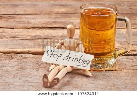 Stop drinking alcohol concept. Human wooden dummy sitting with message near glass of beer.