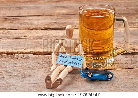 Do not drink and drive concept. Human wooden dummy sitting with beer, car, old wooden background.