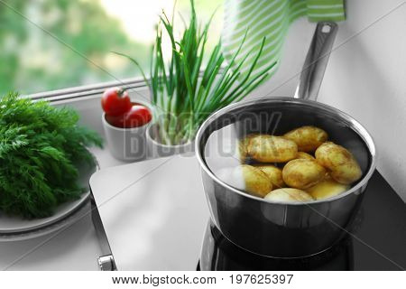 Metal pot with potato on induction cooker in kitchen poster