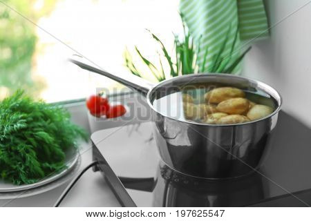 Metal pot with potato on induction cooker in kitchen