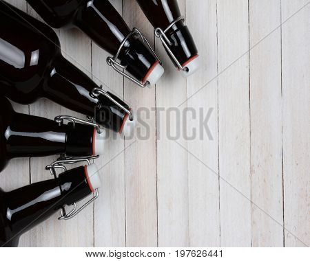 Top view of a group of swing top beer bottles on their sides on a rustic white wood background.