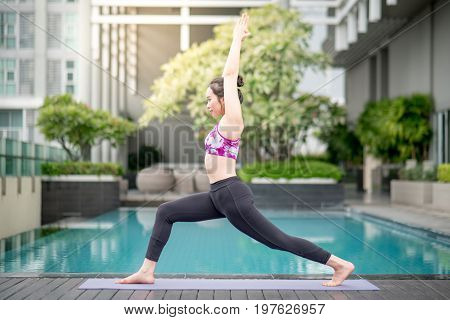 Beautiful young Asian woman doing yoga exercise with Virabhadrasana I posing near swimming pool. Healthy lifestyle and good wellness concepts