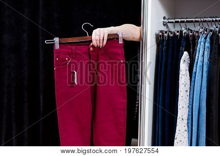 Woman trying on pants in a clothing store reaching out hand from a fitting room holding trousers.