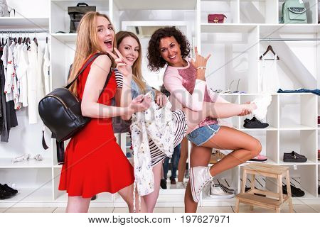 Cool stylish girls having fun standing in funny pose expressing true positive emotions in trendy clothing shop with racks of accessories and clothes in background.