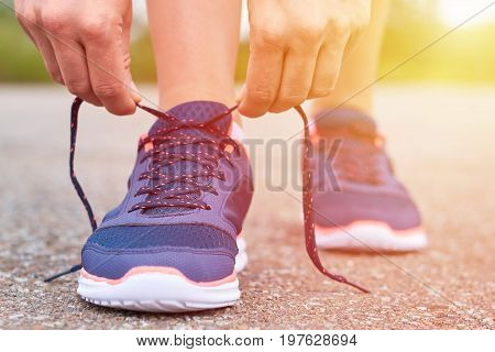 Girl Ties Up Shoelaces In Sneakers On Road While Jogging, Legs And Sneakers, Sunlight