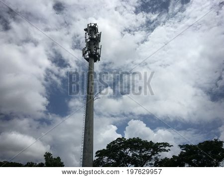 Tall cellular tower against cloud background. Mobile technology equipments.