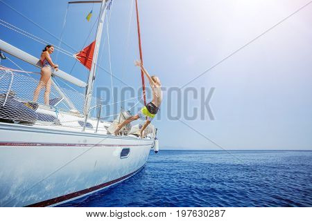 Boy with his sister jump in sea of sailing yacht on summer cruise. Travel adventure, yachting with child on family vacation.