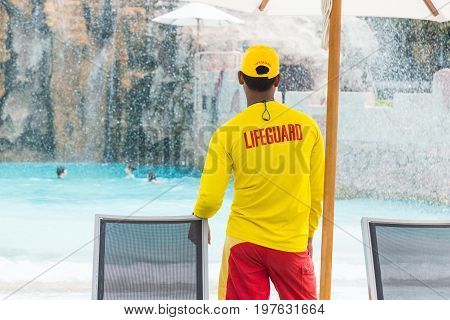 back side of lifeguard man wearing yellow lifeguard shirt and cap standing on duty