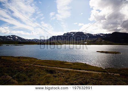 Landscape with mountains lake sky and clouds in Norway.