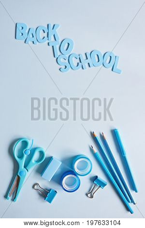 Back to school supplies and letters on light blue background.